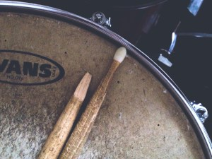 Worn Snare drum with drum sticks, one of which is broken