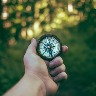 Image of a hand holding out a compass