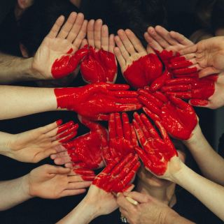 Multiple hands with red paint come together to form a heart