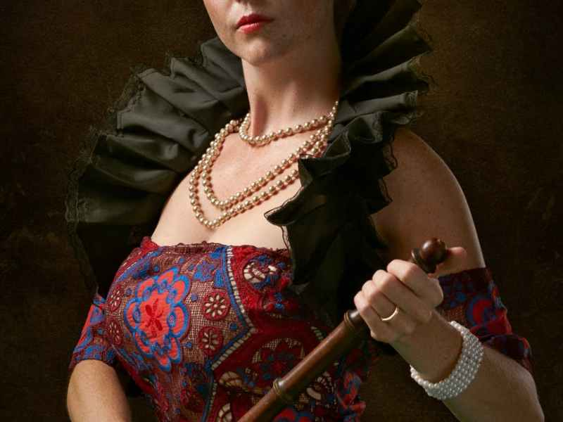 photo of woman looking while holding a wooden baton