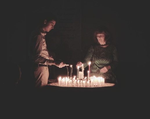 Two people lighting candles in a dark room