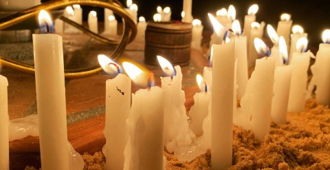 Many white candles burning close together in the dark.