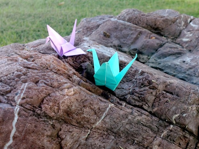 Two paper origami cranes on a stone