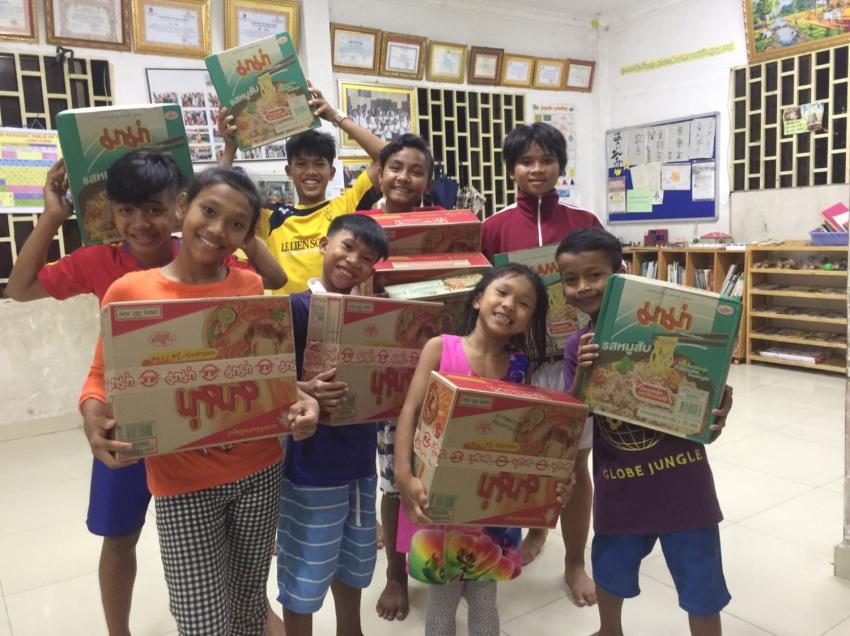 孤児院の子どもたちに渡した物資を抱えて笑っている子どもたち