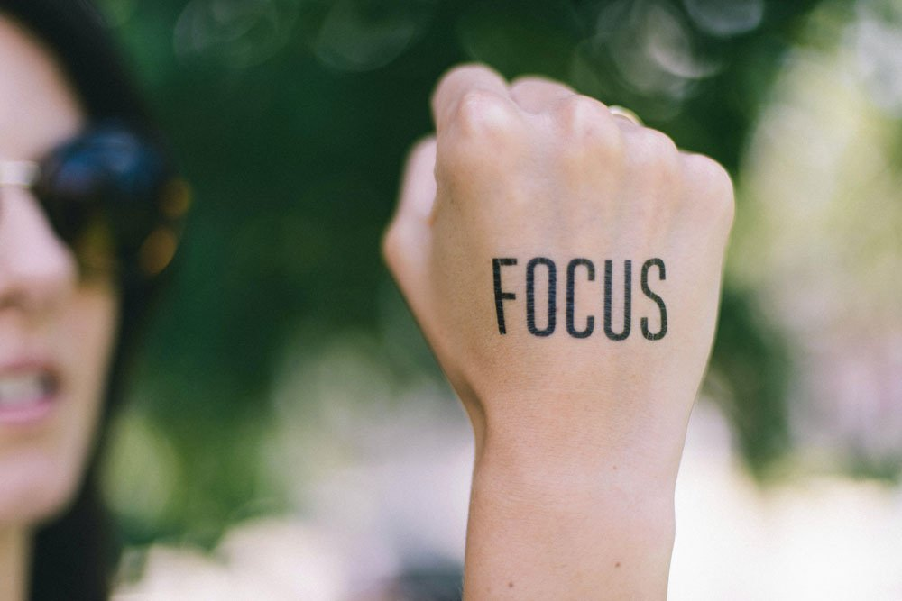 woman making a fist with text tattoo that says focus