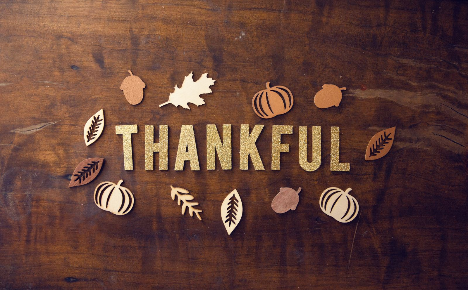 "The word ""Thankful"" on a wooden background with leaves around it"