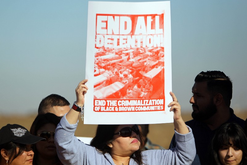 A demonstrator holds a sign before a performance by Colombian musician Juanes and singer John Legend, in front of a detention center in Eloy, Arizona, Wednesday, Jan. 20, 2016. CREDIT: AP Photo/Ricardo
