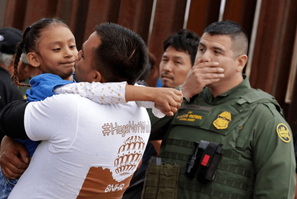 A man embraces a child as a Border Patrol agent.png