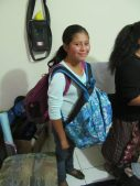 Jennifer is carrying 2 backpacks to help out her sister