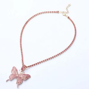 collier papillon de couleurs rose sur une table