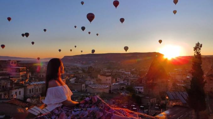 A girl enjoying sunset on a rooftop. Enjoy her life