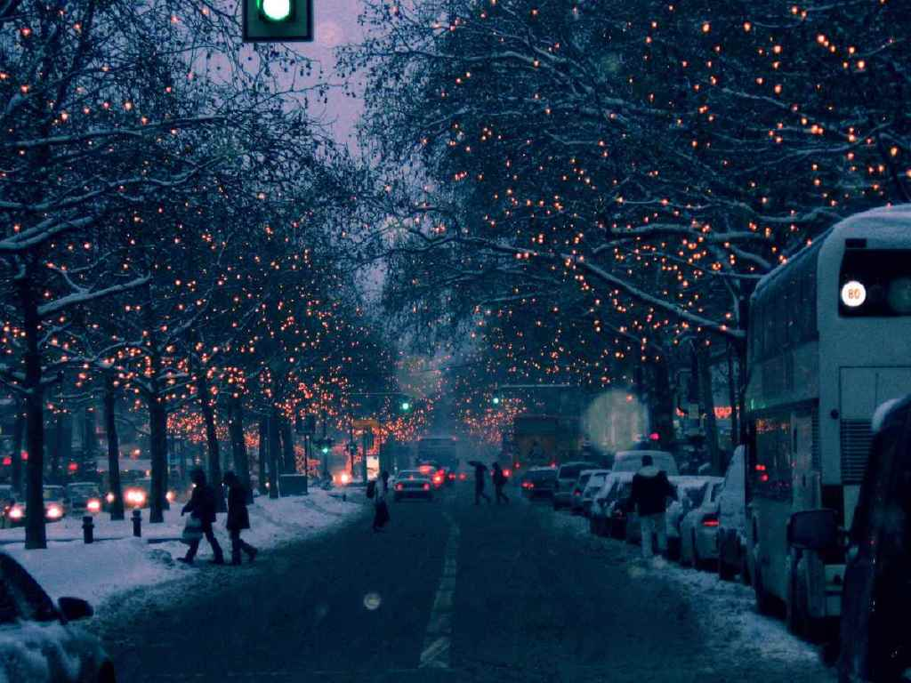 A beautiful Street with christmas decorations, everything calm, people are out in snowy streets happyly.