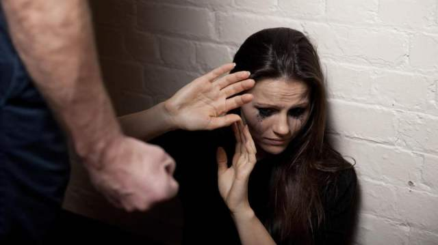 Female abuse victim cowering with clinched foist over her