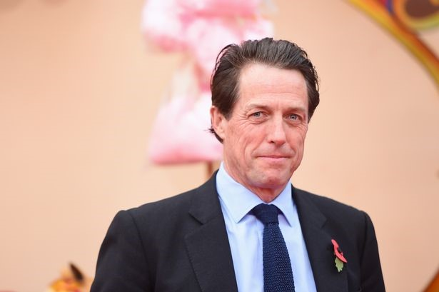 Actor Hugh Grant in a suit and tie with a poppy on