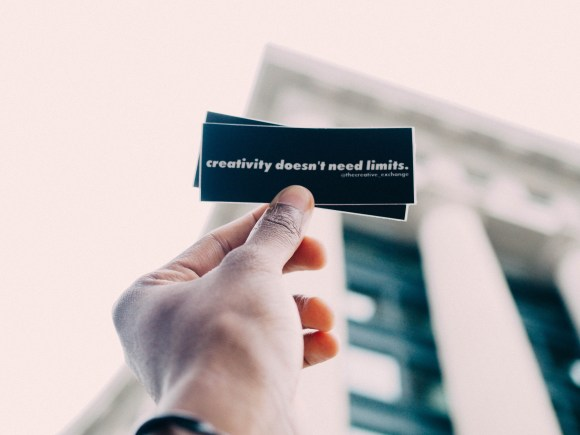 """Photo of a hand holding stickers that say """"Creativity doesn't need limits."""""""
