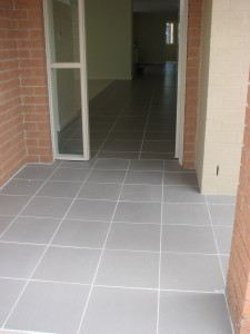 A grey tiled porch leads seamlessly into the home without any change in level.