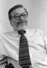 black and white photo of Ron Mace. He is wearing glasses and has a beard. He is wearing a light coloured shirt and a dark neck tie