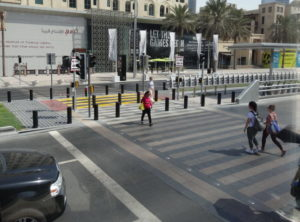 A wide pedestrian crossing covering four lanes of traffice