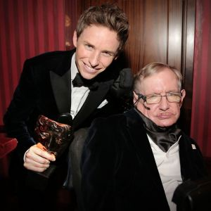 Eddie Redmayne played the part of Stephen Hawking in the film. They are posing for the camera with Eddie holding an Oscar.