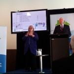 An Auslan interpreter stands next to the speaker on stage.