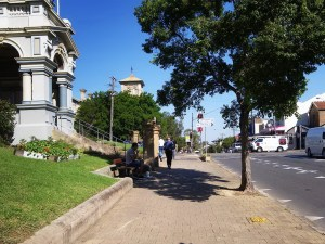 A street scene in Leichhardt, Sydney. It shows a heratig building on the left, a wide paved footpath and a large tree on the right. In the distance you can see a person walking and in the mid ground in a footpath inset is a person sitting on a seat.