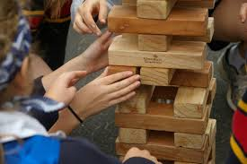image shows people putting block of wood together to create a tower