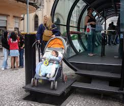 Woman with a baby stroller using the platform lift to get onto the raised bus stop platform .The bus stop is a tube shaped shelter