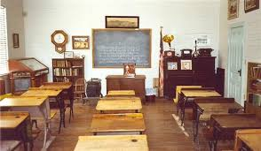 picture of empty classroom showing wooden desks and a small blackboard