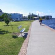 picture of a wide paved walkway along the estuary showing a bike rider, a seat and grass.