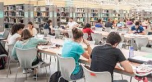 view of university of seville library with students sitting at desks. bookcases are in the background.