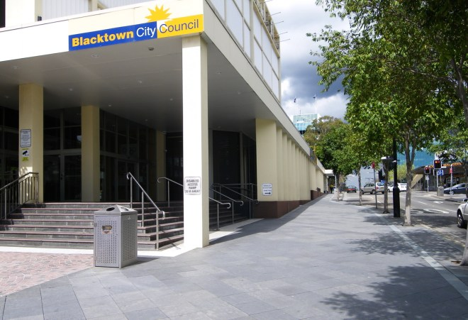 Street scene showing stepped entrance to a council building with a disabled access sign on the pillar.