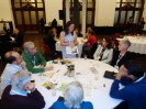 People are seated around a large table and Elise Copeland from New Zealand is leading a Table Topic discussion