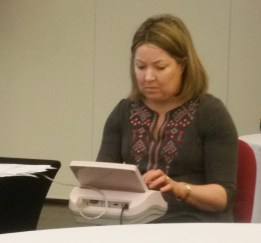 Picture shows Mandy at her stenographer machine composing the live captioning at the conference