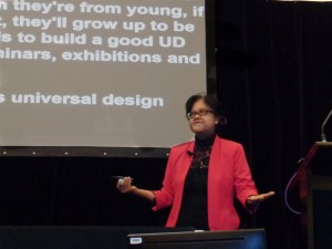 Siam Imm in a bright pink jacket making her presentation at the UD Conference