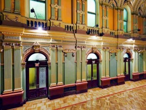 A view of the vestibule of the Sydney Town Hall showing arched doorways and upper storey windows. The colours are classical heritage colours, mustard yellow, pale green and dark red.