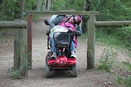 picture of a woman on a mobility scooter trying to get under a barrier constructed to prevent vehicles and bicycles from entering the path