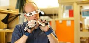 A man wearing simulation gloves and glasses tries to open a sticky note pad