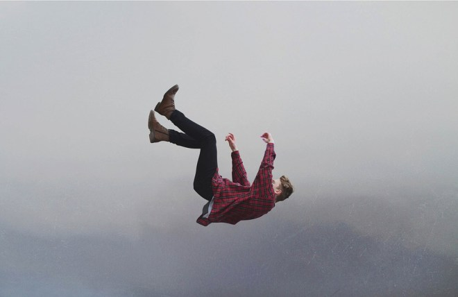 shows a man in mid air falling backwards, legs and arms pointed upward. He is wearing a red shirt, the background is cloudy or foggy