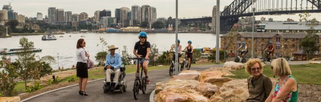 Landscape view of Barangaroo Parkland showing a pedestrian, wheelchair user, cyclist and pram pusher