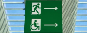 Green emergency egress signs showing running figure and wheelchair figure