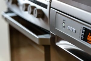 close up of the knobs on a stainless steel oven and a diswasher