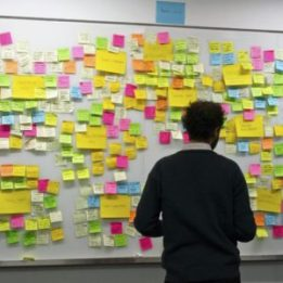 a man stands in front of a wall covered in bright coloured post it notes which have different ideas and actions