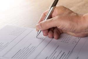 Picture of a hand holding a pen and filling in boxes on a survey form