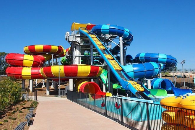 Red and yellow striped tubes twisted with blue and yellow tubes with a big water slide
