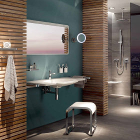 A bathroom setting showing a wall mounted vanity bsin, a stool and in the background a hand held shower and a shower seat. There is also a mounted magnifying mirror.