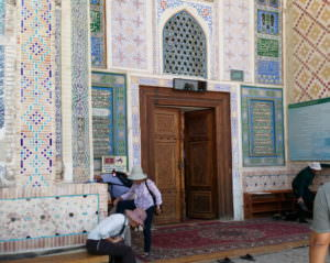 People at the mosque door taking off their shoes. One person is sitting