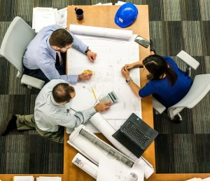 aerial view of three people at a desk looking at a set of construction drawings