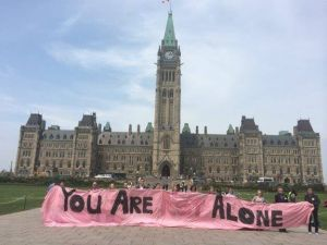 A group of people standing holding a pink banner with the words You are Not Alone, but you can't see the word NOT because it is in pale red and blends into the background colour