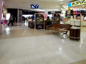 Picture of a shopping mall with a plain grey floor and shops on each side. Thre is a woodend bench with armrests and backrest. In the distance you can see more shops.