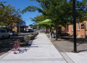 Street scene showing level footpath, shade treas, shade umbrella and lots of seating